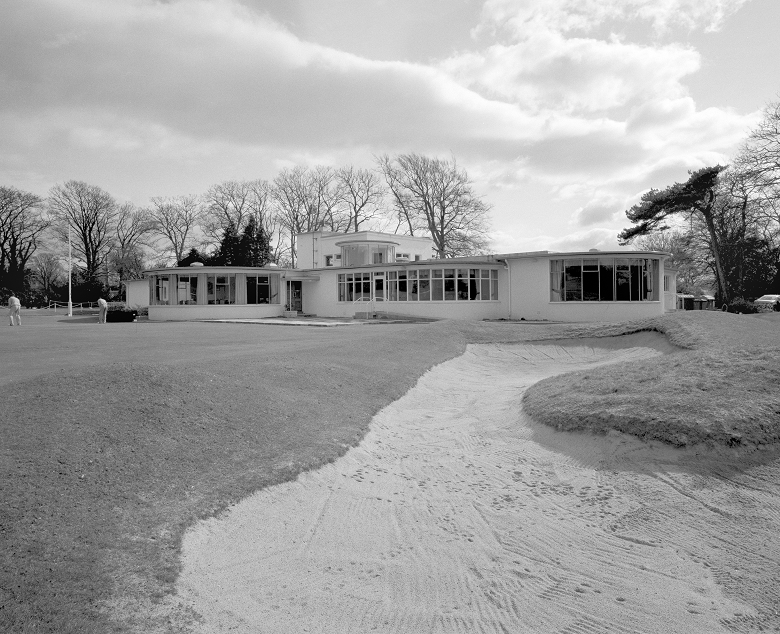 Black and white photo of an Art Deco golf cllubhouse with a bunker in the foreground