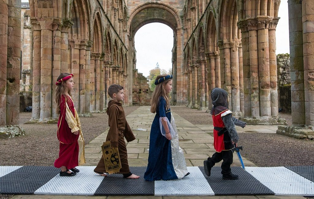 Four children in historical costumes recreate The Beat'es Abbey Road album cover at Jedburgh Abbey