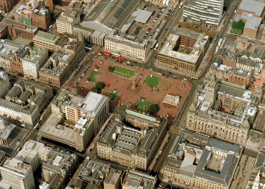 A bird's eye view of a city, focused on a large square with a red floor and a tall statue in the centre