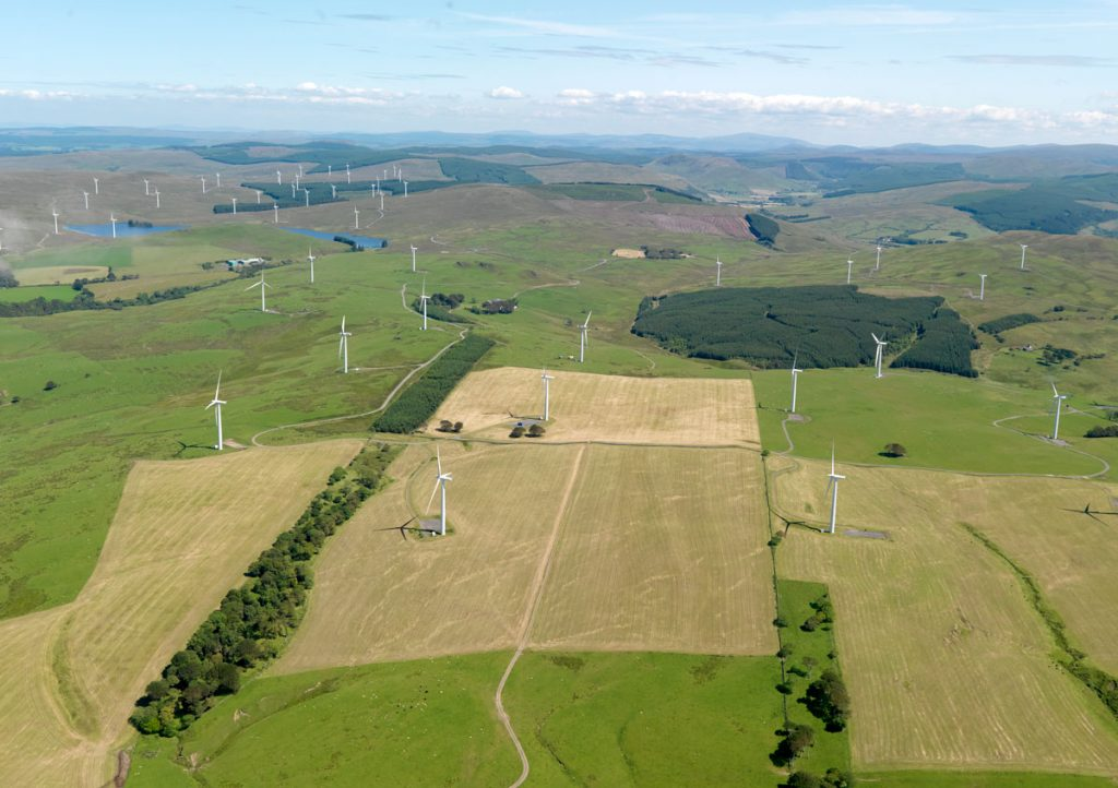 A bird's eye view over fields and a wind farm filled with turbines.