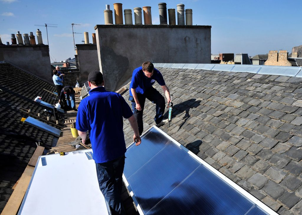 Two men stand on a rooftop securing solar panels to tiles. Chimney pots can be seen in the distance.