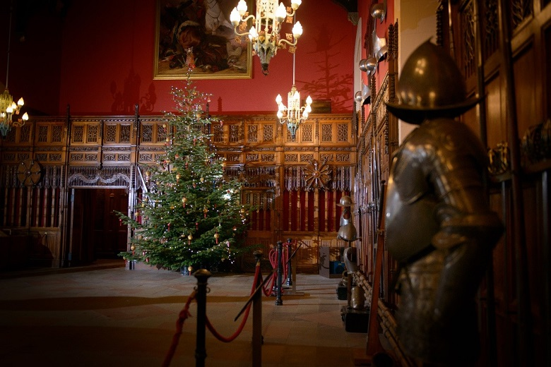 The Great Hall in Edinburgh Castle decorated with historic portraits, suits of armours, weaponry and the festive addition of a fir tree