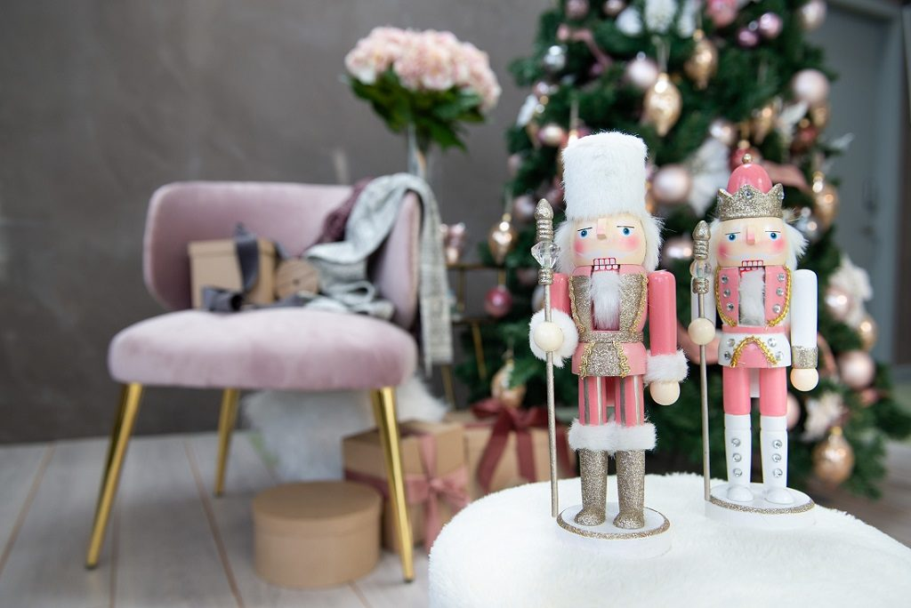 Tree decoration figurines wearing pink outfits placed in front of a Christmas tree