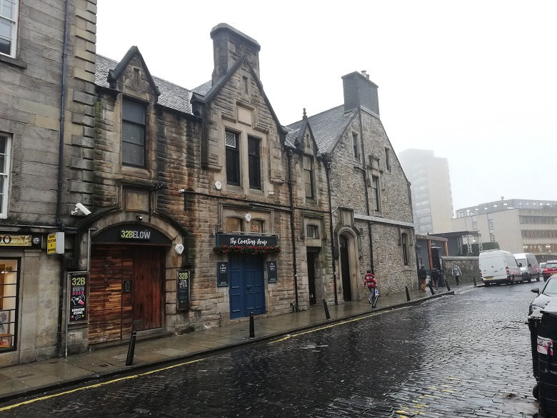 An 18th century building in Edinburgh converted into a number of pubs. The street in front is cobbled.