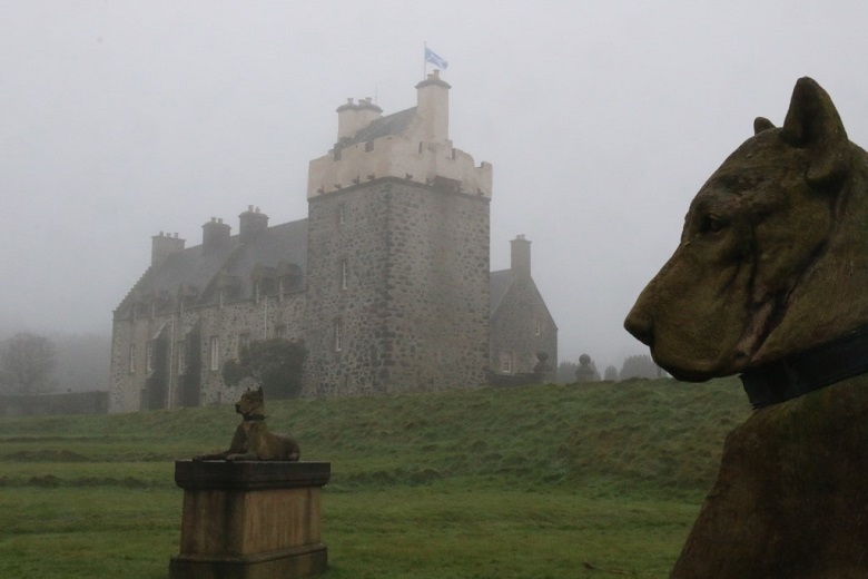 Two stone carved dogs in front of a castle building shrouded in mist