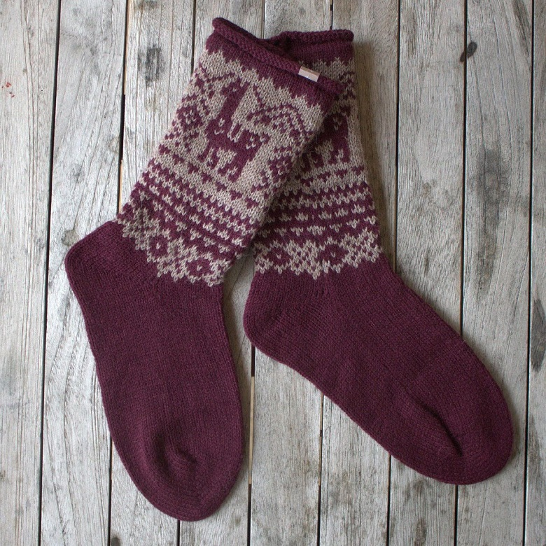 A pair of red knitted socks featuring an alpaca design