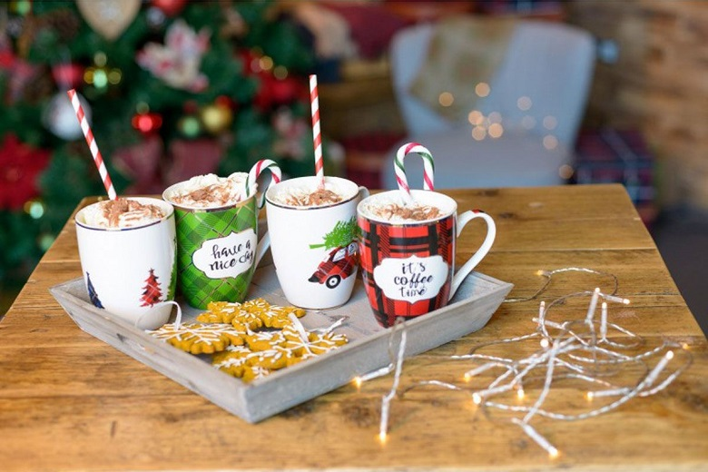 For Christmas themed mugs on a tray containing hot drinks