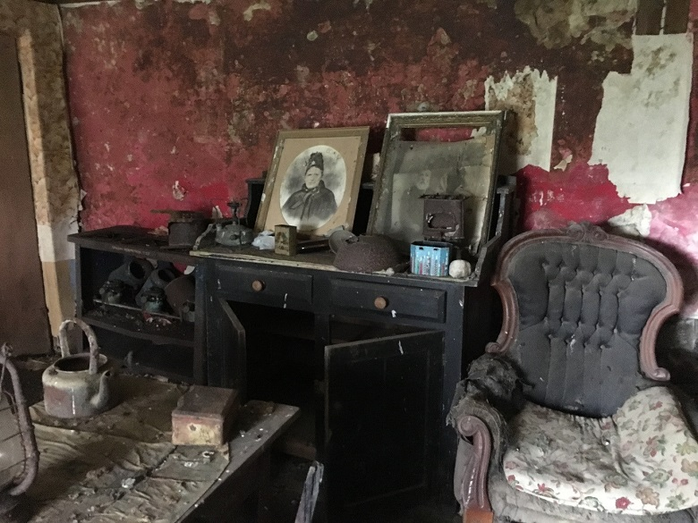 Interior of a crofthouse with an abandoned chair, kettle, portrait and other items