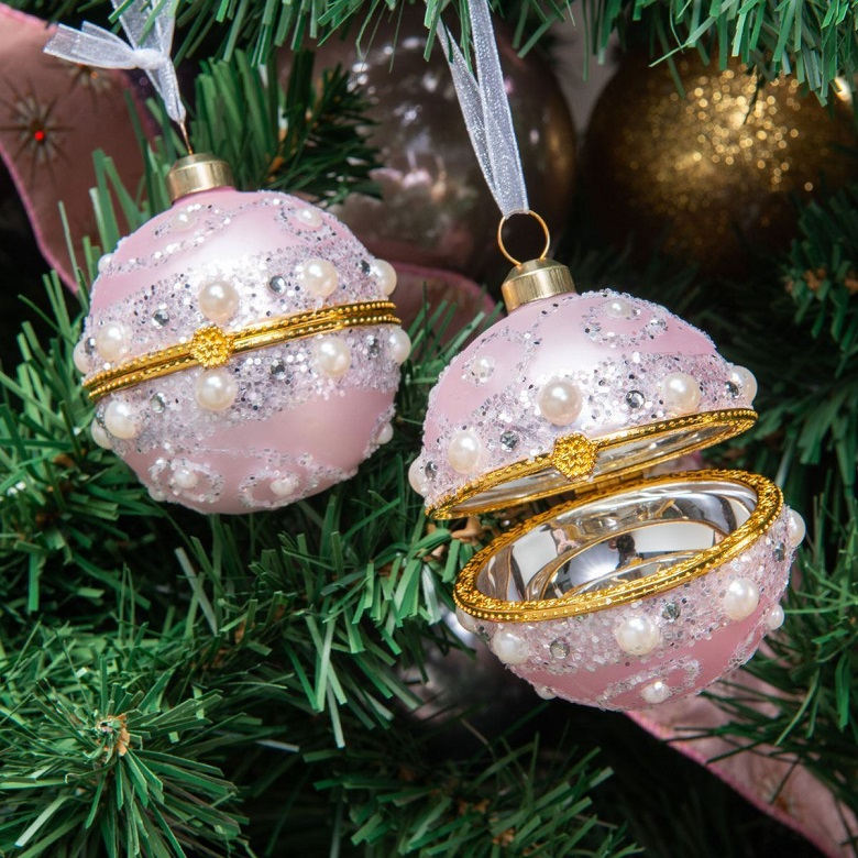 Two pink and gold baubles hanging from a Christmas tree
