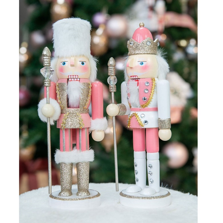 A pair of wooden Christmas nutcracker figures wearing pink outfits