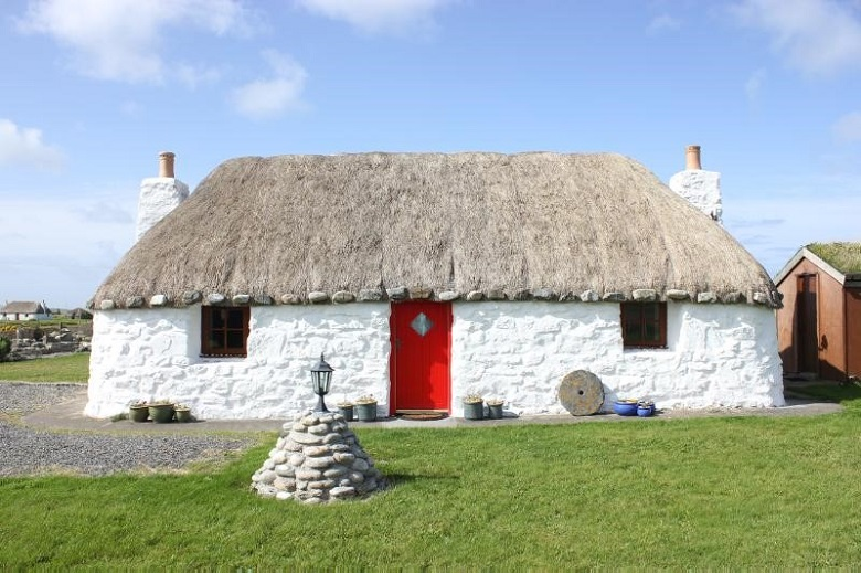 A small thatched cottage with a red door