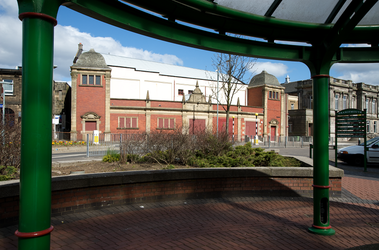 A distinctive red brick theatre building framed by a green shelter or canopy on the opposite roadside