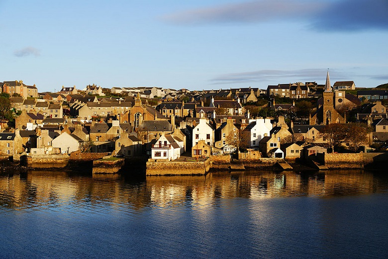 Photo of Stromness harbour with closely-packed houses and church buildings