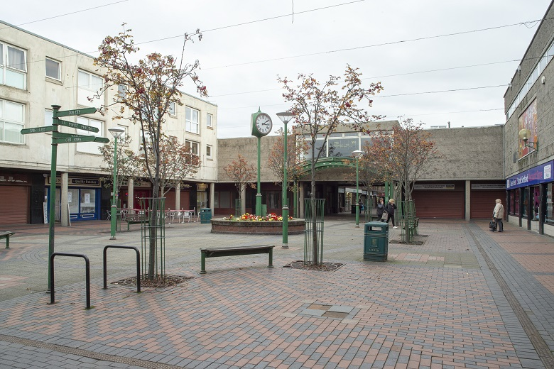 Interior courtyard in a 1970s shopping centre featuring a green clock, flowerbeds, signposts, benches, bicycle racks and bins