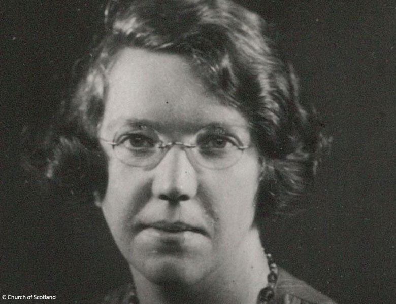 black and white photo of a woman with waved hair and round glasses