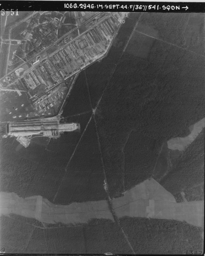 Aerial photo showing mainly woodland but in the top left corner a concentration camp complex is visible