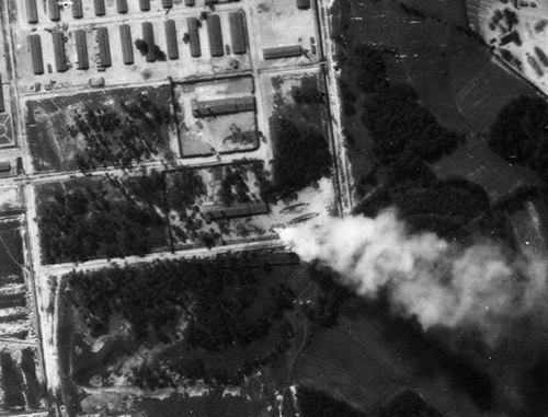 aerial photo showing the corner of the Auschwitz complex with smoke blowing across the bottom right corner