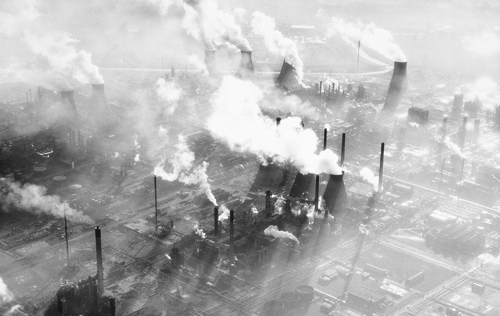 Archive aerial view of factory chimneys emitting large plumes of whote smoke inot the sky above Grangemouth