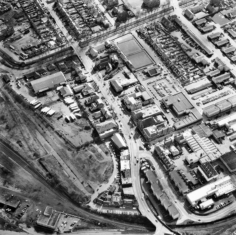 Aerial view of a town showing car parks, a bus garage, bowling greens and housing
