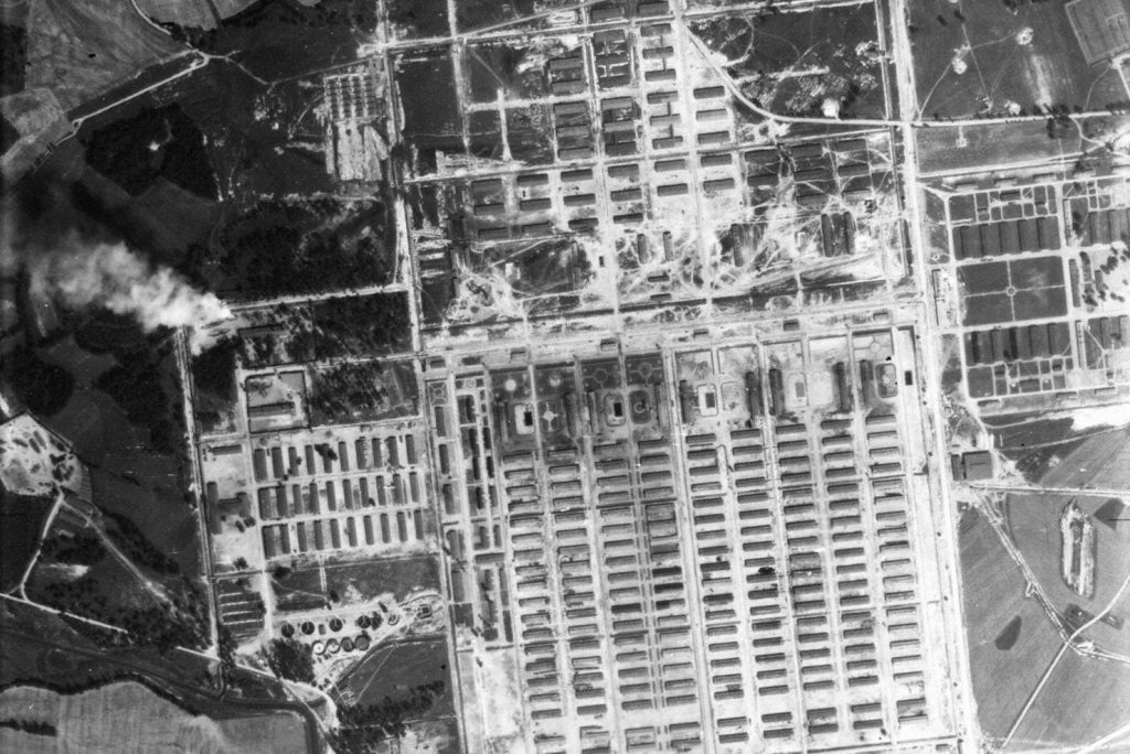 aerial image showing concentration camp huts laid out in a grid format. In the top left corner a plume of smoke can be seen rising from the extermination camp.