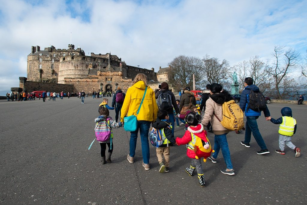 A group of you children with high visibility vests on visit Edinburgh Castle