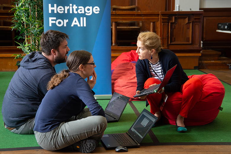 "Three people sit on the ground with laptops in front of a banner that says ""Heritage For All"""