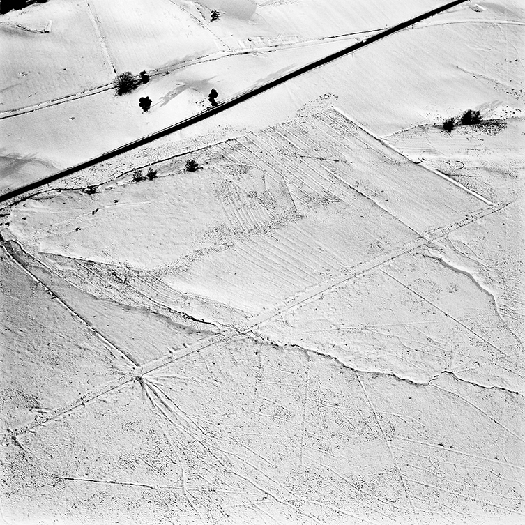 view from above showing a snow covered field with the outline of a road beneath the snow
