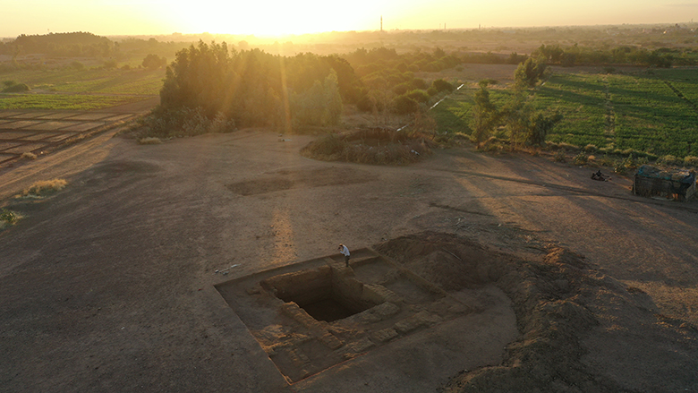 aerial photo of the sun rising over archaeological excavations.