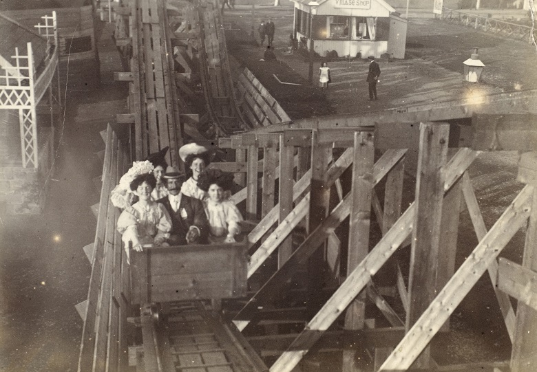 Archive photo of a well-dressed family in a cart on a historic wooden roller coaster