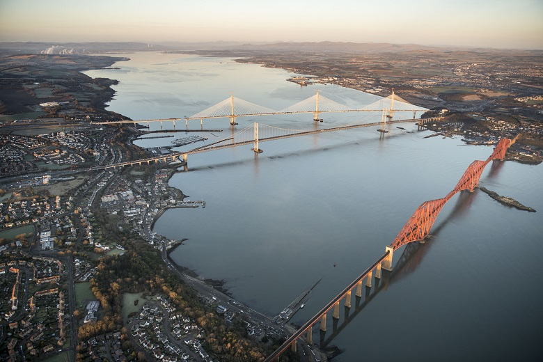 Aerial photo of the Forth Bridge, the Forth Road Bridge and the Queensferry Crossing on a clear day. Blackness Castle can be made out in the background.