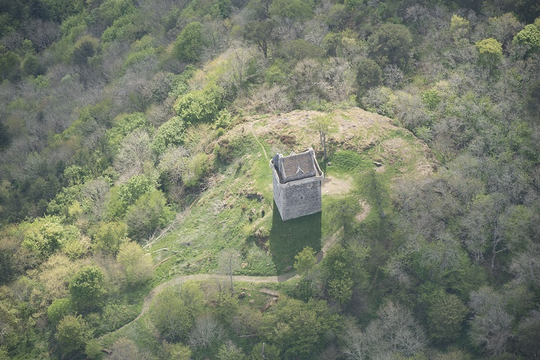 Aerial view of paths leading through moorland to a well-preserved tower house