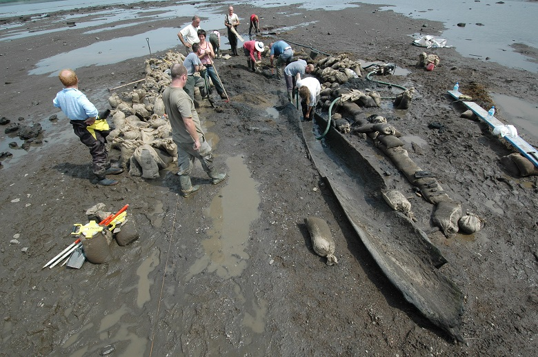 A team of archaeologists working to excavate a boat on a riverbank