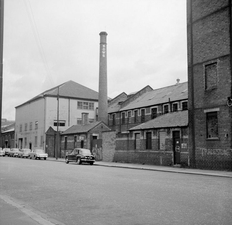 Archive black and white photo of cars parked in a street beside a sawmill