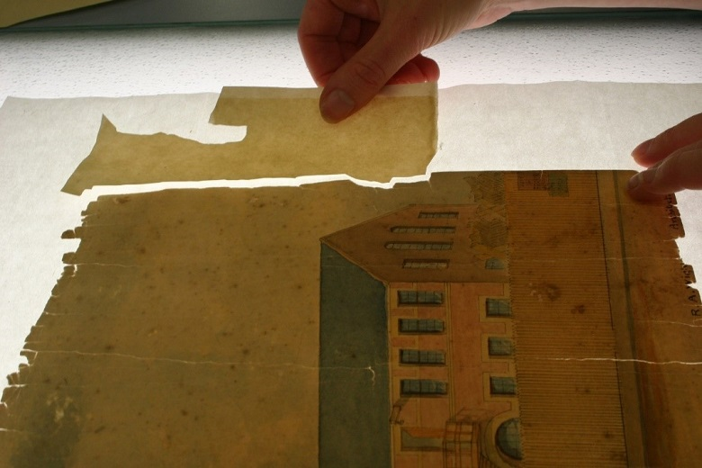 Close up photo of a conservator patching a damaged painting