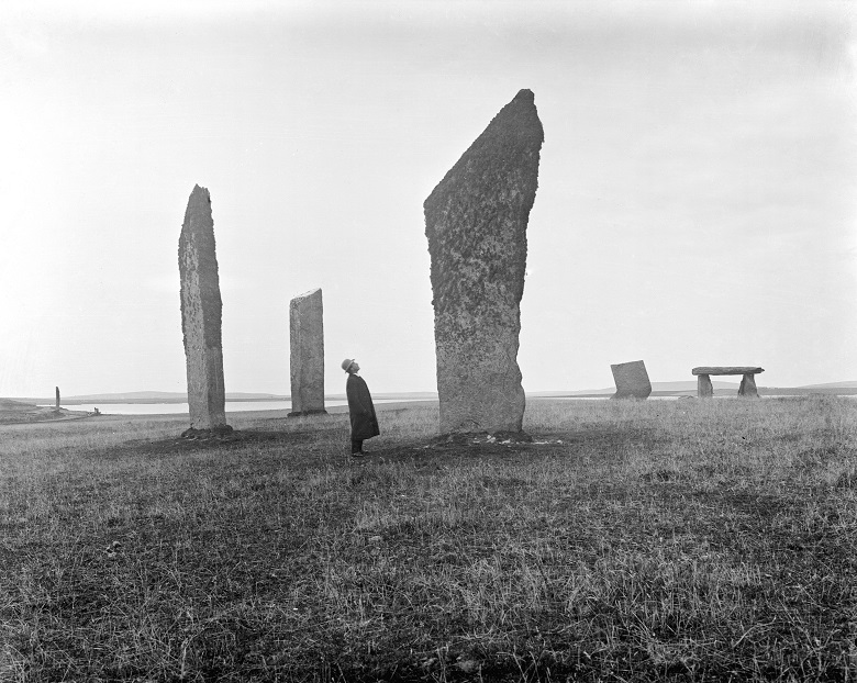 Black and white archive photo of a man in a coat and hat looking up at a prehistoric standing stone