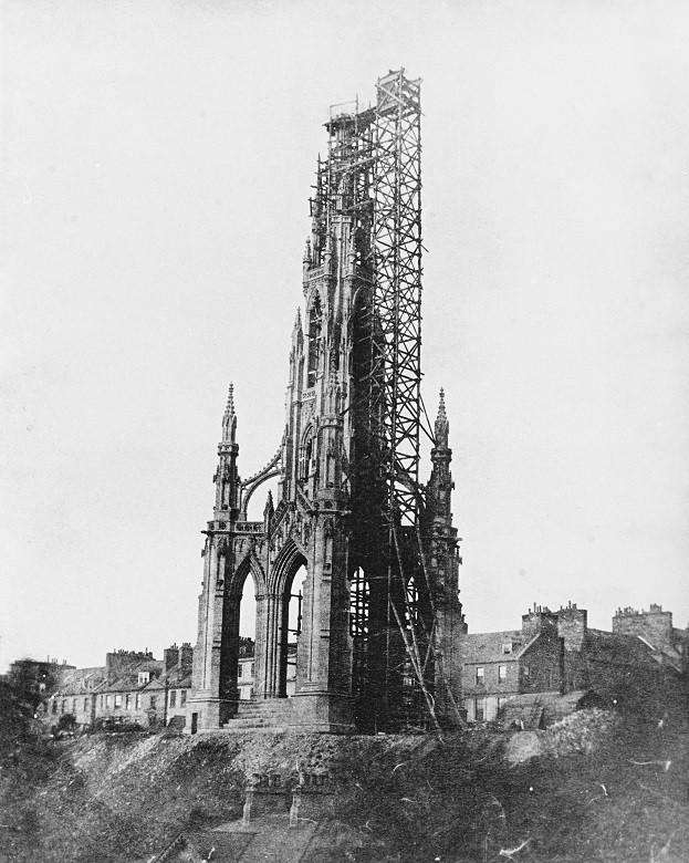 Black and white archive photo of the Scott Monument under construction. The monument is about half completed, with scaffolding along one side. Long-demolished buildings can be seen on Princes Street in the background.