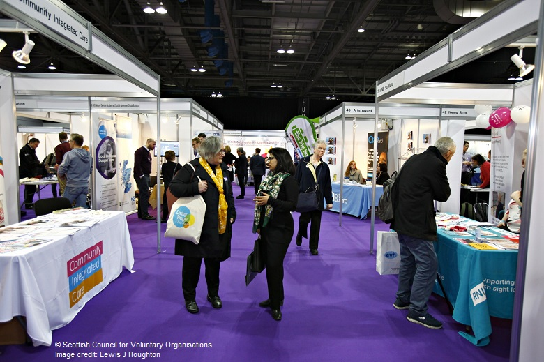 delegates chat at an exhibition stand