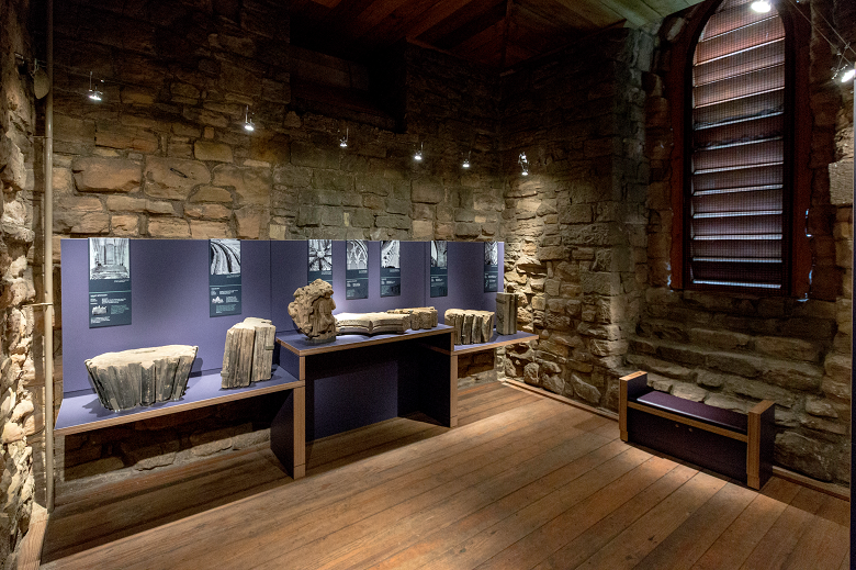 An exhibition of old, large stones inside a historic stone building