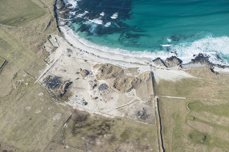An aerial photo historic settlement by the sea. The coast is being eroded away.