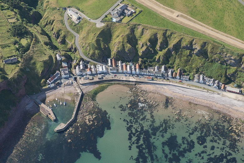 An aerial photo of a row of houses by the sea