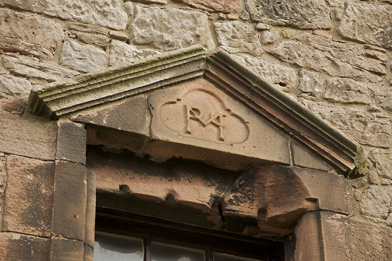 A carved window lintel with the letters M, M and C.