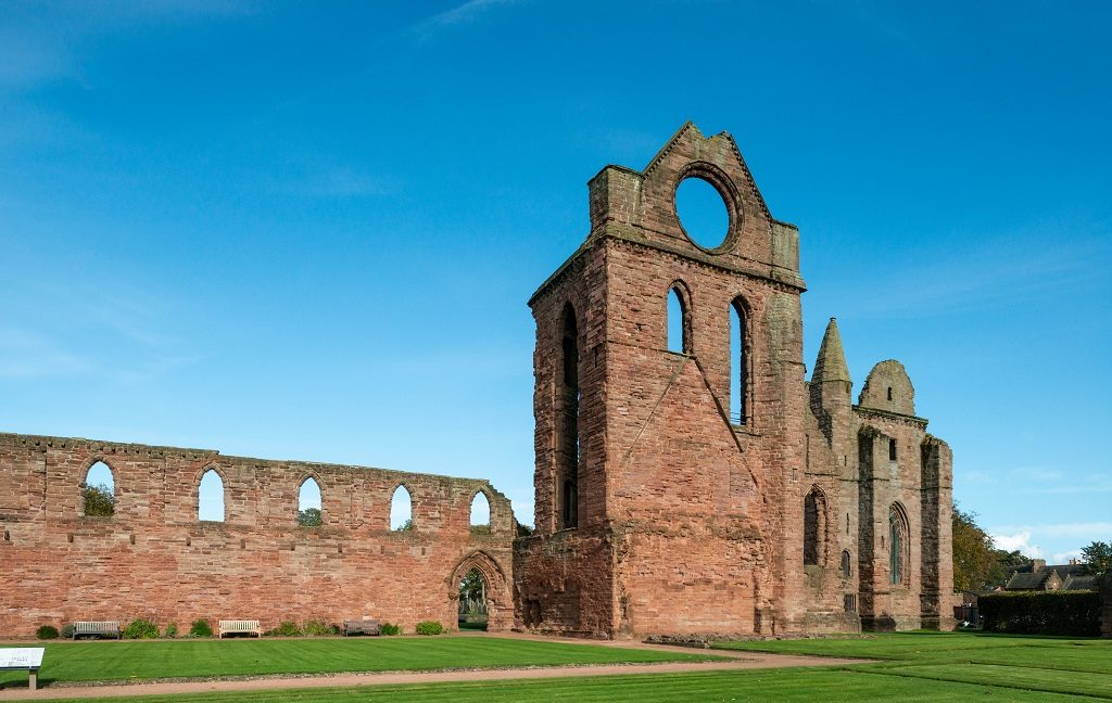The ruins of Arbroath Abbey under a blue sky, showing its tower with distinctive round window