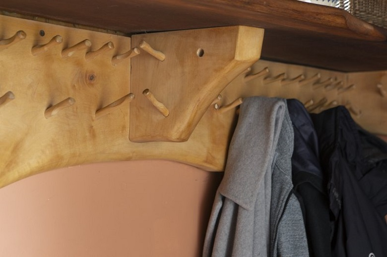 Hand-carved wooden coat pegs inside The Steading