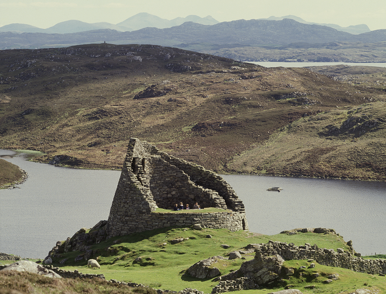 View of a broch on a rocky outcrop in front a small loch with the sea beyond