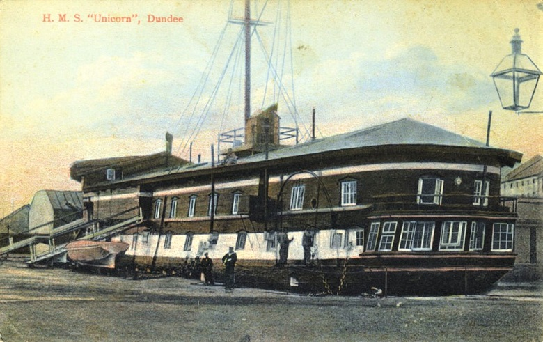 A vintage postcard depicting the HMS Unicorn on the waterfront in Dundee with two men and an old-fashioned lamppost in the foreground
