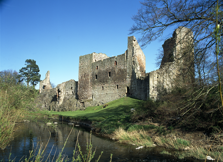 Imposing ruins of a large castle beside a river
