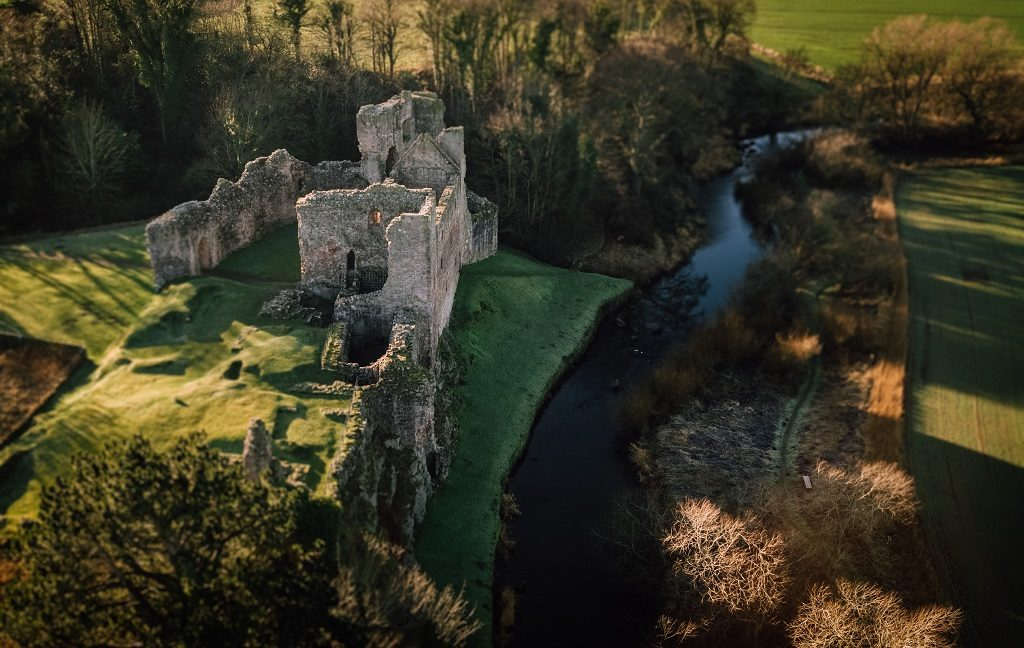 A drone photo of Hailes Castle beside a river
