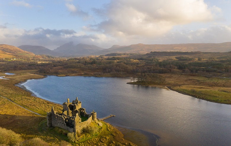 Drone photo of Kilchurn Castle beside Loch Awe with cloud-covered mountains in the background