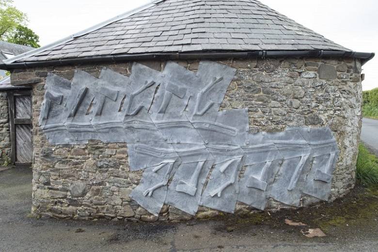 Lead depictions of axes on a stone wall near the entrance to The Steading