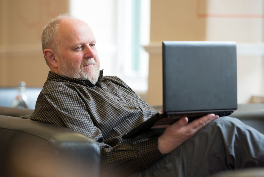 A man with a white beard sits on a sofa and looks at a laptop, smiling